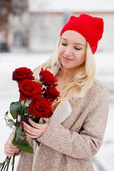 Junge schöne blondine mit strauß roter rosen am valentinstag
