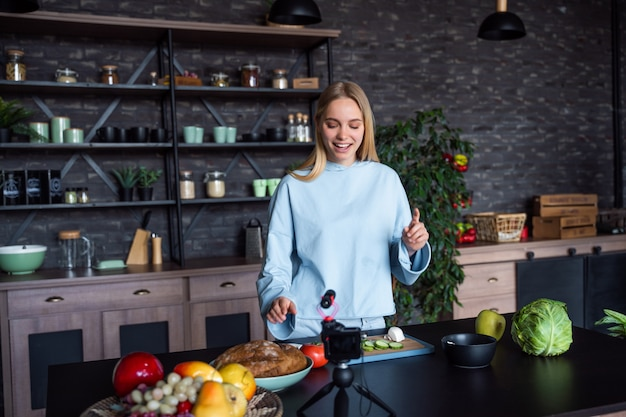 Junge schöne blondine nimmt videos auf, während sie in der küche kocht