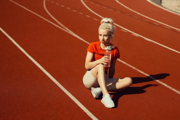 Junge schöne blondine sitzt auf einer joggingstrecke mit einer flasche wasser in den händen