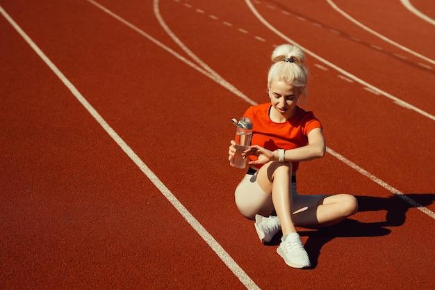 Junge schöne blondine sitzt mit einer flasche wasser auf einer joggingstrecke und schaut auf ihre uhr