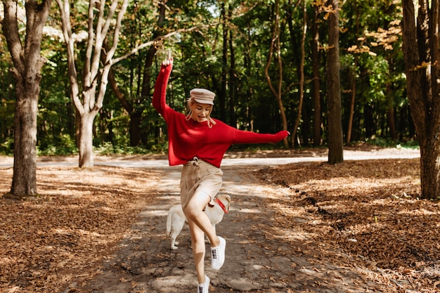 Junge schöne blondine tanzt im herbstpark mit spaß.