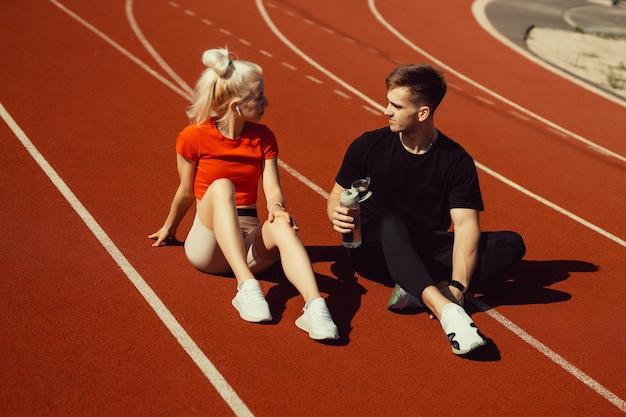 Junge schöne blondine und ein kerl sitzen mit einer flasche wasser auf einer joggingstrecke und unterhalten sich