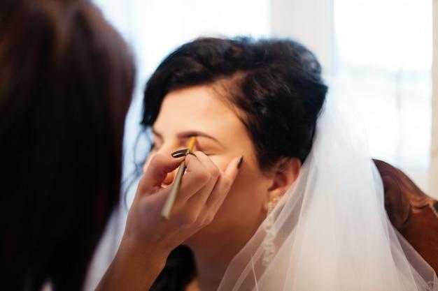 Junge schöne braut, die hochzeitsschminke durch maskenbildner anwendet