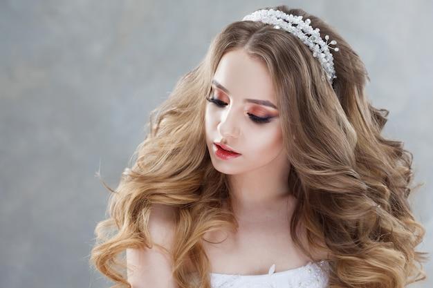 Junge schöne braut mit luxuriösen locken. hochzeitsfrisur mit tiara.