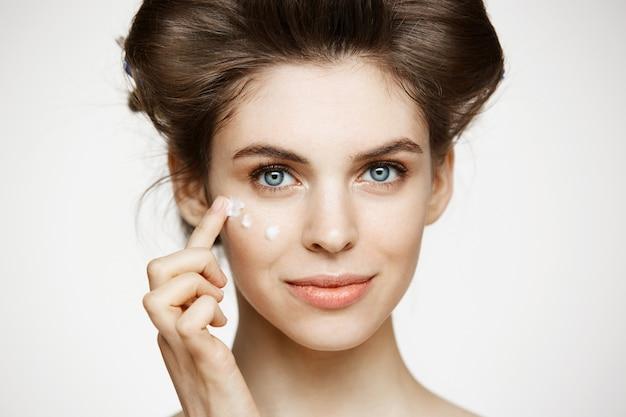 Junge schöne brünette frau in den lockenwicklern, die cremiges gesicht lächeln. gesichtsbehandlung. schönheitsgesundheit und kosmetologie.