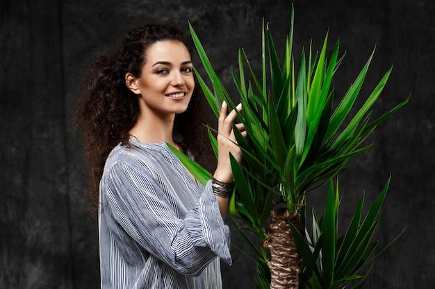 Junge schöne brünette frau in tropischen pflanzen über graue wand