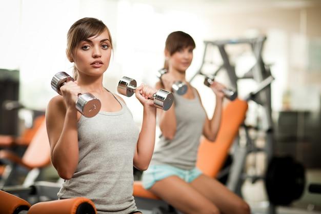 Junge schöne brünette frau instruktor in sportbekleidung zeigt, wie man hanteln zu einem anderen mädchen im fitnessstudio verwendet