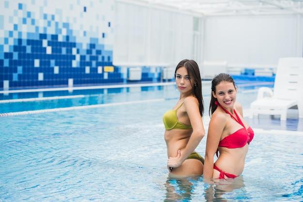 Junge schöne brünette frauen im schwimmbad drinnen