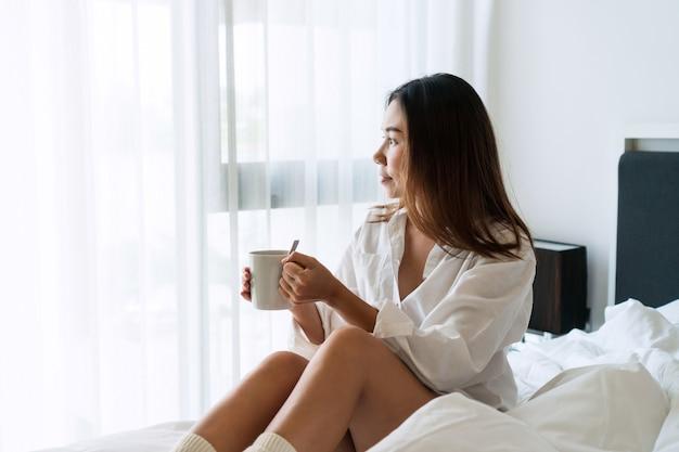 Junge schöne brünette haarfrau in weißen hemdpyjamas, die kaffee trinken, während auf dem bett am morgen sitzen.