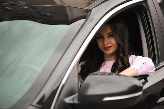 Junge schöne brünette im schwarzen auto.