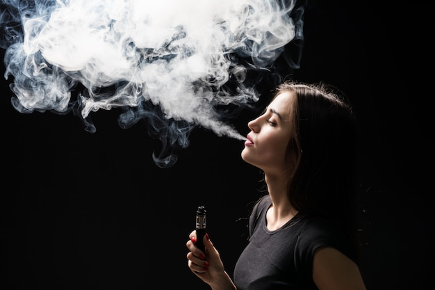 Junge schöne brünette raucht, verdampft e-zigarette mit rauch an der schwarzen wand
