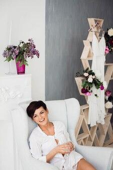 Junge schöne brünette sitzt auf dem weißen großen stuhl