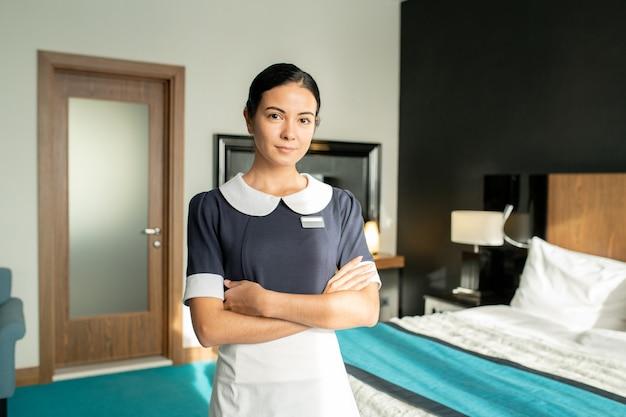 Junge schöne brünette zimmermädchen in uniform, die ihre arme mit der brust verschränkt hält, während sie im hotelzimmer gegen das bett steht