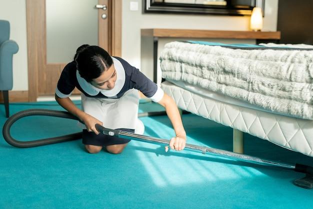 Junge schöne brünette zimmermädchen in uniform mit staubsauger beim reinigen des blauen bodenbelags unter dem bett im hotelzimmer