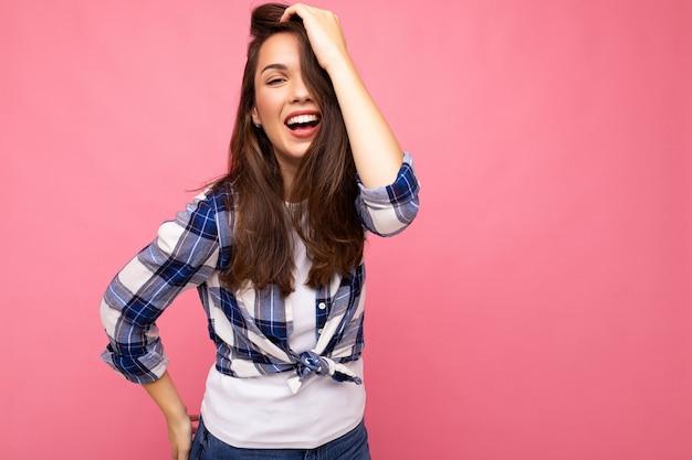 Junge schöne brunetfrau. trendige dame im lässigen sommer-hipster-hemd. positives weibchen zeigt aufrichtige gesichtsgefühle. lustiges modell isoliert auf rosa hintergrund mit freiem speicherplatz