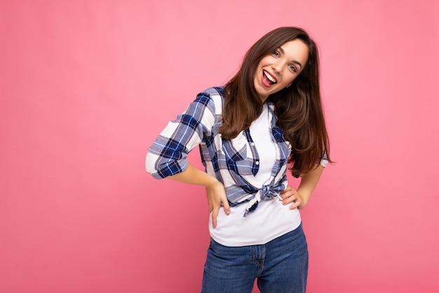 Junge schöne brunetfrau. trendige dame im lässigen sommer-hipster-hemd. positives weibchen zeigt aufrichtige gesichtsgefühle. lustiges modell isoliert auf rosa hintergrund mit freiem speicherplatz.