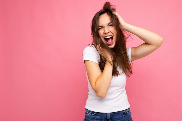 Junge schöne brunetfrau. trendige dame im lässigen weißen sommer-t-shirt zum mock-up. positives weibchen zeigt aufrichtige gesichtsgefühle. lustiges modell isoliert auf rosa hintergrund mit freiem speicherplatz. Premium Fotos
