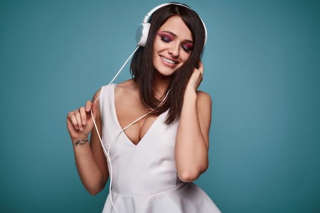 Junge schöne brunettefrau im kleid mit kopfhörern