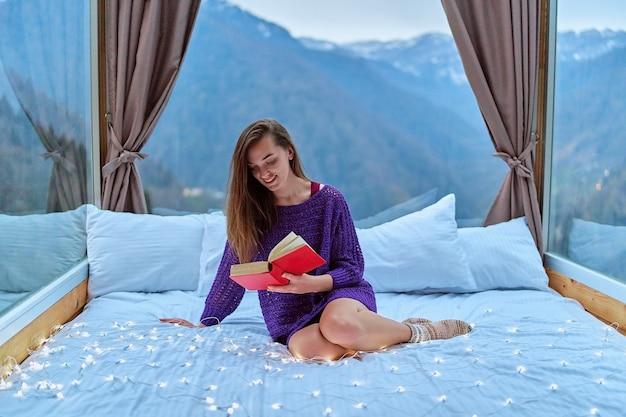 Junge schöne charmante glückliche süße lächelnde frau, die leidenschaftlich gerne aufregende buchromane liest, während sie auf dem bett mit blick auf die berge sitzt