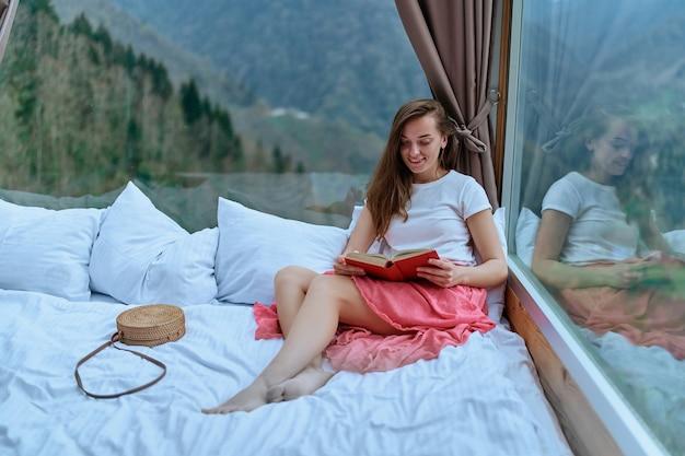 Junge schöne charmante glückliche süße lächelnde romantische frau, die leidenschaftlich gerne aufregende buchromane liest, während sie auf dem bett mit bergblick liegt
