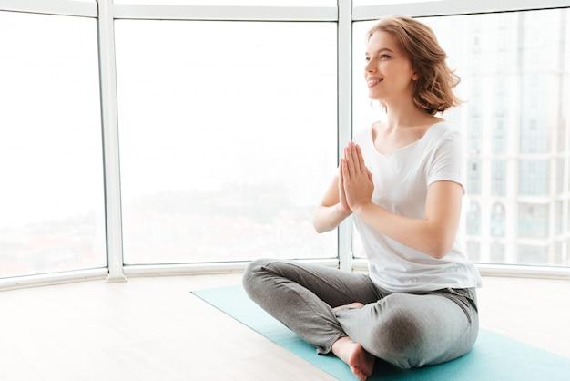 Junge schöne dame, die nahe fenster sitzt, machen yogaübungen.