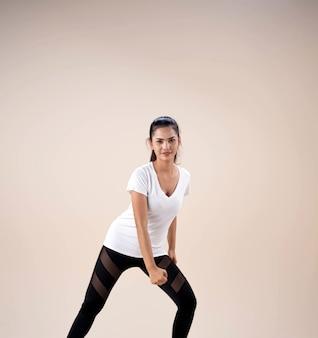 Junge schöne dame, die sportbekleidung trägt, stehende füße auseinander knien und faust neben ihre beine legen, tanztraining für übung, mit glücklichem gefühl