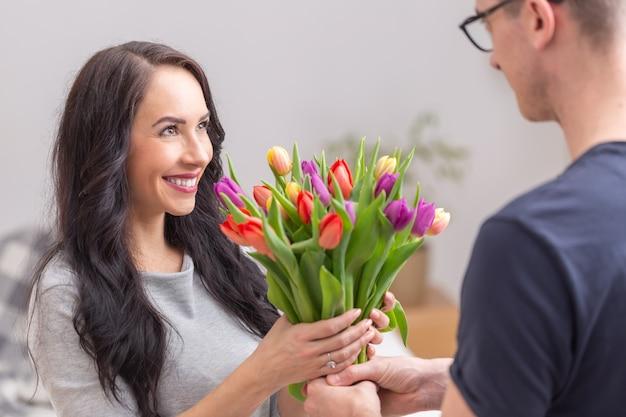 Junge schöne dame, die während des nationalen frauentages einen bunten strauß voller tulpen von ihrem ehemann oder freund erhält.
