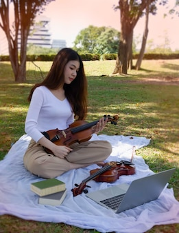 Junge schöne dame hält geige in der hand, schaut zum laptop und lernt, wie man akustisches instrument spielt.