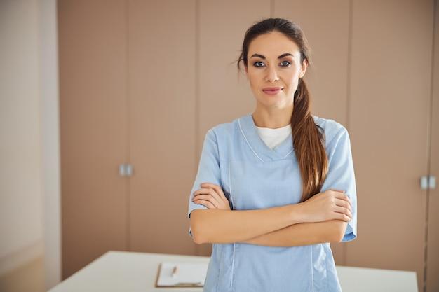 Junge schöne dame in medizinischer uniform posiert im büro
