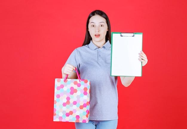 Junge schöne dame mit einkaufstasche und klemmbrett