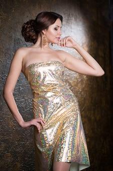 Junge schöne elegante frau im goldenen abendkleid mit schöner frisur