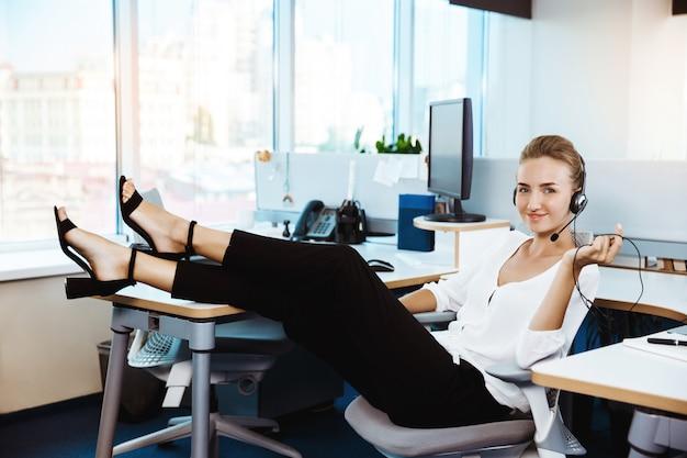 Junge schöne erfolgreiche geschäftsfrau, die sich am arbeitsplatz, im büro ausruht