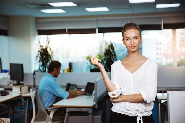 Junge schöne erfolgreiche geschäftsfrau lächelnd, posierend, über büro