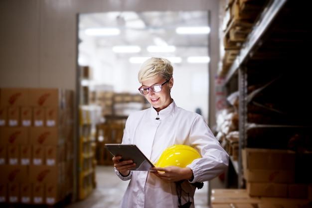 Junge schöne erfreute engagierte weibliche arbeiterin betrachtet tablette und hält ihren gelben helm, während in der nähe eines stapels von pappkartons im fabriklagerraum stehen.