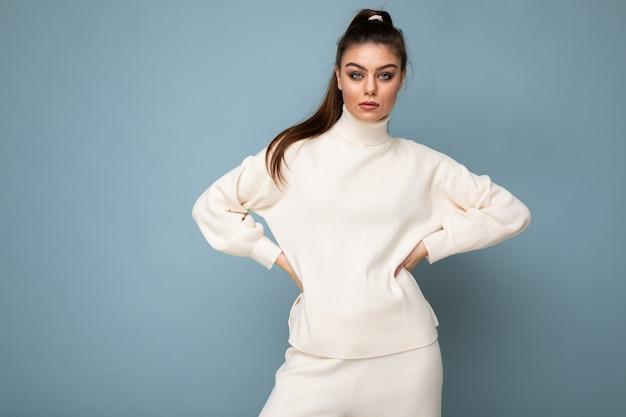 Junge schöne europäische modefrau, die weißen pullover lokalisiert über blaue wand mit ernstem ausdruck auf gesicht trägt. speicherplatz kopieren