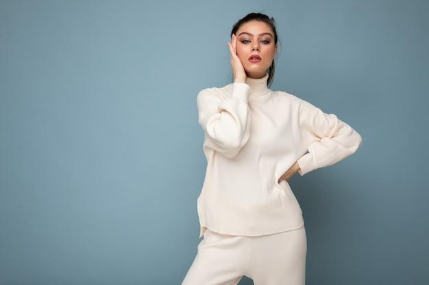 Junge schöne europäische modefrau mit weißem pullover auf blauem hintergrund mit