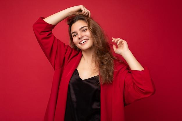 Junge schöne europäische stilvolle brünette frau mit schwarzem blusenoberteil und roter strickjacke isoliert