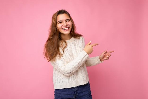 Junge schöne europäische stilvolle brünette frau mit weißem winterpullover isoliert über rosa