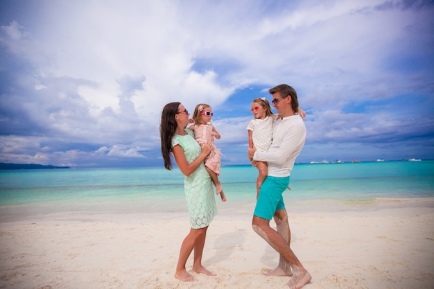 Junge schöne familie mit zwei kindern, die einander auf tropischen ferien betrachten