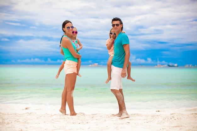 Junge schöne familie mit zwei kindern, die kamera auf tropischen ferien betrachten
