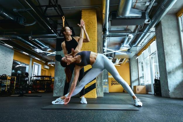 Junge schöne fitnessfrau, die sich vor dem training aufwärmt, trainiert mit einem personal trainer im fitnessstudio?