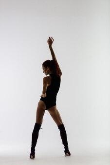 Junge schöne flexible frau in schwarzem overall und high heels posiert in einem tanzstudio.