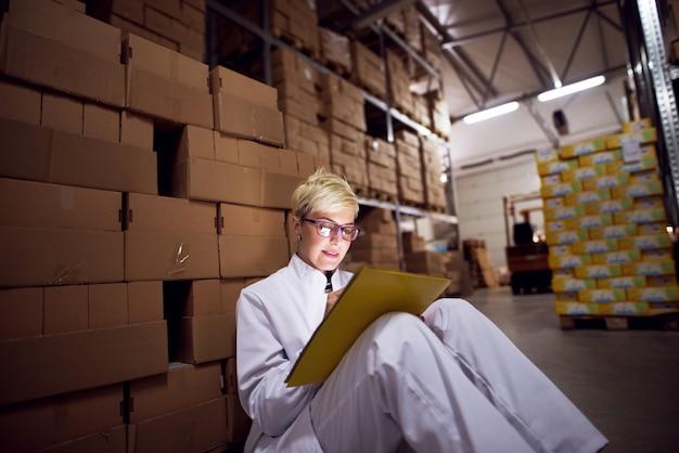 Junge schöne fokussierte arbeiterin füllt einen papierkram auf dem gelben ordner, der an ihren schoß gelehnt ist, während sie auf dem boden sitzt und sich gegen einen stapel brauner pappkartons in der fabrik lehnt