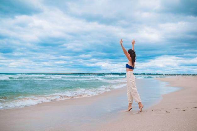 Junge schöne frau am strand bei windigem und bewölktem wetter