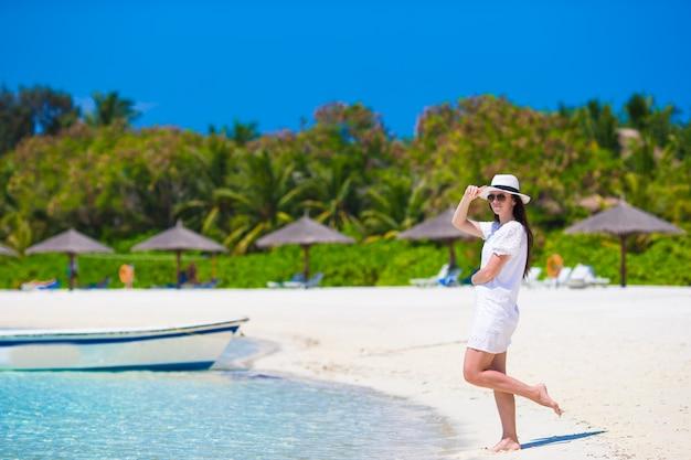 Junge schöne frau am strand während der tropischen ferien