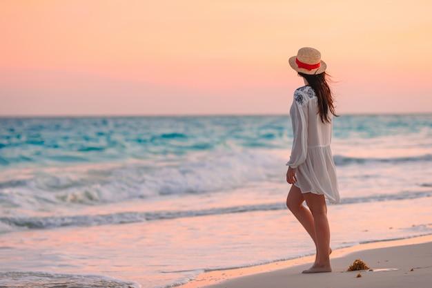 Junge schöne frau am tropischen strand im sonnenuntergang.