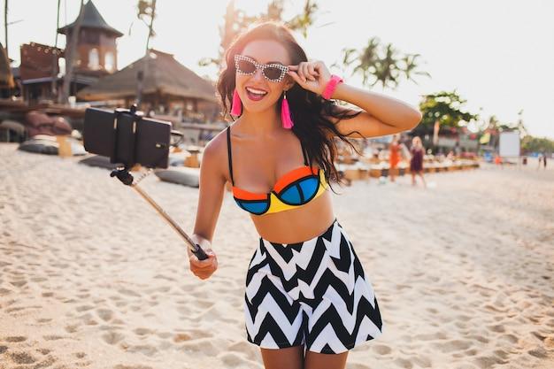 Junge schöne frau am tropischen strand, selfie-foto auf smartphone, sonnenbrille, stilvolles outfit, sommerferien, spaß machend, lächelnd, glücklich, bunt, positive emotion