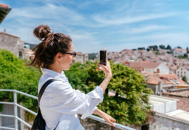 Junge schöne frau auf einem balkon, der eine kleinstadt in kroatien übersieht