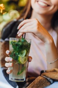 Junge schöne frau auf einer sommerterrasse in freizeitkleidung trinkt cocktail. mit einer decke bedeckt