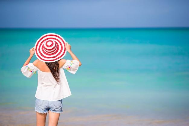 Junge schöne frau auf tropischem strand des weißen sandes. hintere ansicht des kaukasischen mädchens